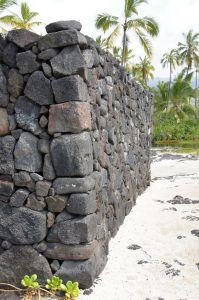 Ancient Hawaiian volcanic stone wall  on beach at Puuhonua O Honaunau Place of Refuge National Park, Hawaii
